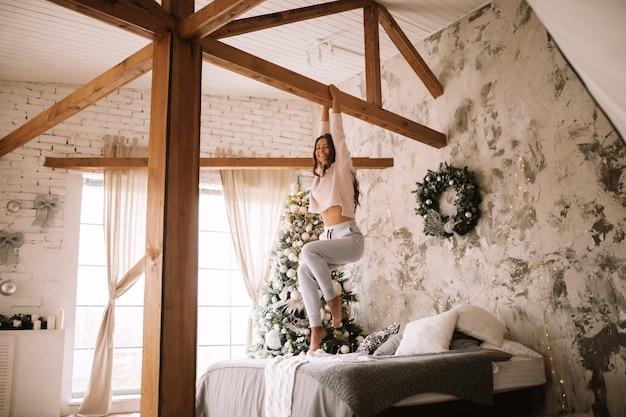 흰색 스웨터와 바지를 입은 멋진 소녀가 새해 나무가 있는 아늑한 장식된 방에서 회색 담요와 흰색 베개가 있는 침대 위의 나무 막대에 매달려 있습니다.
