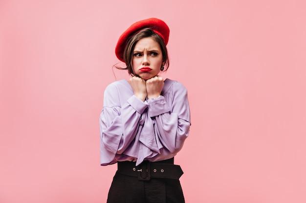 Bella ragazza vestita in camicetta viola, berretto rosso e pantaloni in posa offensiva su sfondo rosa.