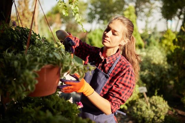 Симпатичная девушка-садовник в солнечный день позаботится о растениях в горшке на веранде в чудесном саду.