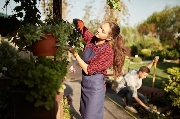 Симпатичная девушка-садовник ухаживает за растениями в горшке на веранде, пока парень в солнечный день роет землю лопатой в чудесном саду.