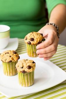 녹색 줄무늬 식탁보에서 아침 식사에 맛있는 초콜릿 칩 머핀을 먹는 좋은 여자 손