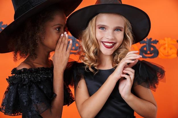 검은 할로윈 의상을 입은 멋진 소녀가 주황색 호박 벽에 격리된 그녀의 귀에 웃고 있는 친구에게 비밀을 속삭였습니다