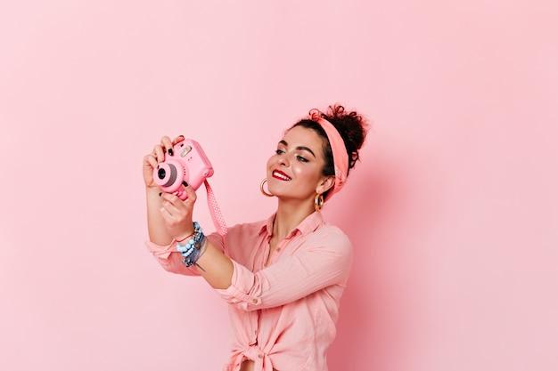 Симпатичная девушка в розовом стиле пин-ап делает фото на мини-камеру на изолированном пространстве.