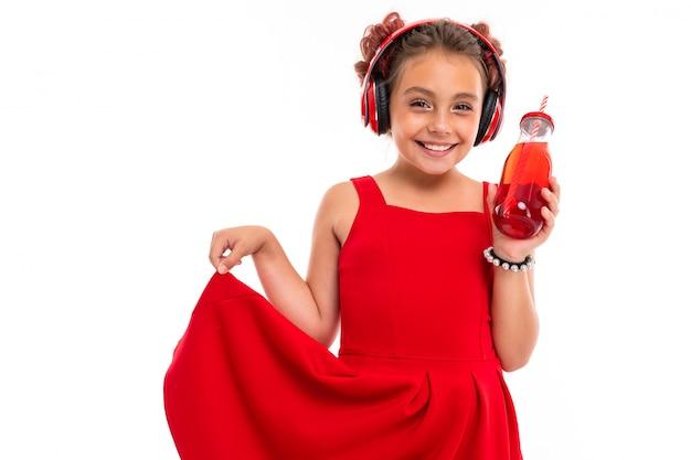 Милая девушка в красном платье с большими наушниками слушает музыку и пьет сок, изолированный на белой стене