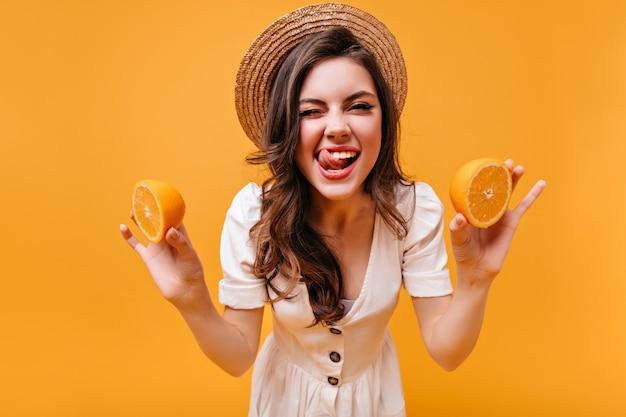 Симпатичная девушка в белом наряде и канотье лизает, подмигивает и держит апельсины.