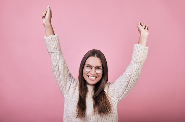 Nice girl in knitted sweater smiles broadly, rejoices in victory