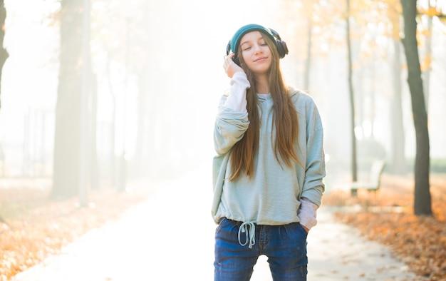 公園でヘッドフォンで音楽を聴いている素敵な女の子