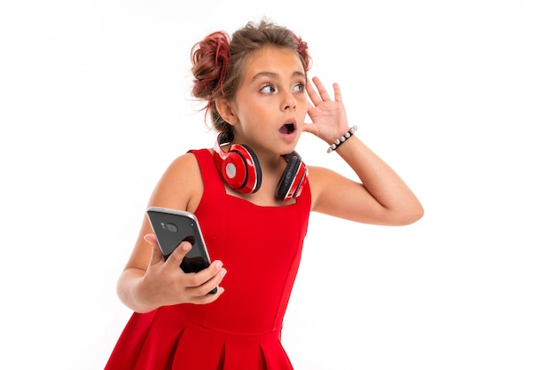 Nice girl in red dress with big earphones heard something isolated on white wall