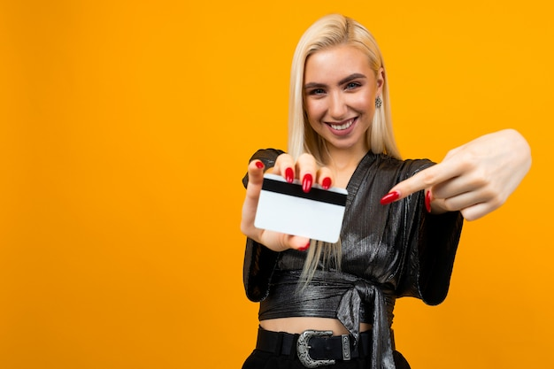 Nice girl shows a credit card with a mock for the bank on a yellow surface with copy space