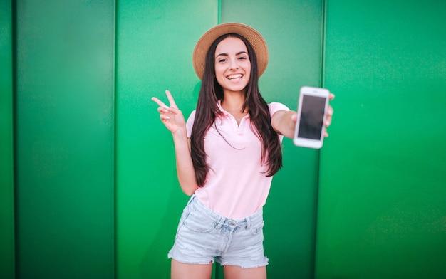 좋은 여자가 서서 카메라에 포즈를 취합니다. 그녀는 손에 흰색 전화를 들고 다른 하나와 조각 기호를 보여줍니다. 여자가 웃고 있다. 녹색과 줄무늬 배경에 고립