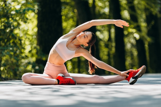 Nice girl stretching in the park outdoor in the morning.