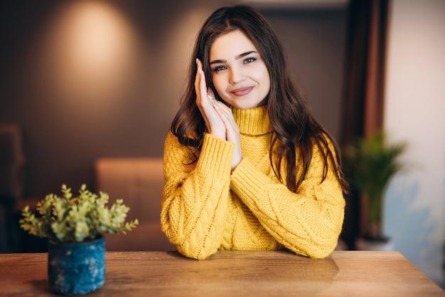귀여운 스웨터를 입고 좋은 여자가 집에서 프리랜서로 일하고 있습니다