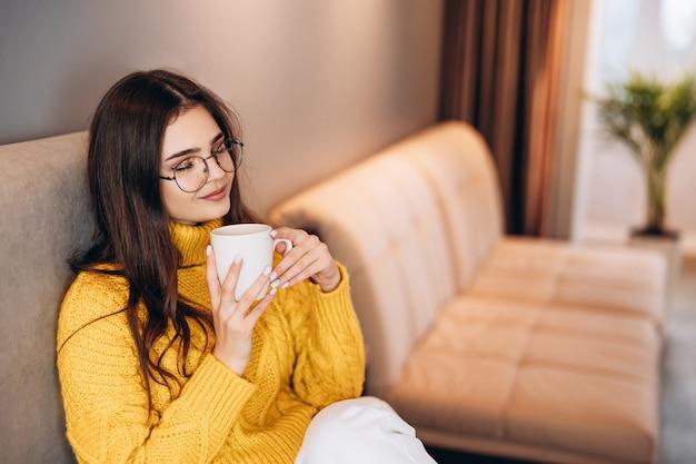 안경과 귀여운 스웨터를 입은 멋진 소녀가 집에서 프리랜서로 일하고 차를 마시는 것을 즐깁니다.