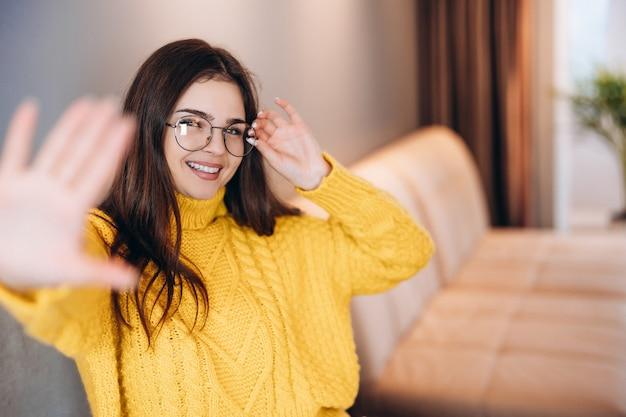안경과 귀여운 스웨터를 입은 멋진 소녀가 집에서 프리랜서로 일하고 있습니다.