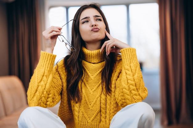 안경과 귀여운 스웨터를 입은 멋진 소녀가 집에서 일하고 있습니다.