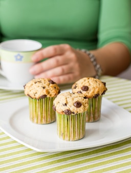 녹색 줄무늬 식탁보로 아침 식사로 컵과 맛있는 초콜릿 칩 머핀을 든 멋진 소녀