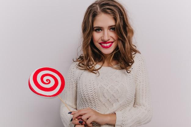 Симпатичная девушка с голубыми глазами и красной помадой улыбается и держит в руках леденец на белой стене