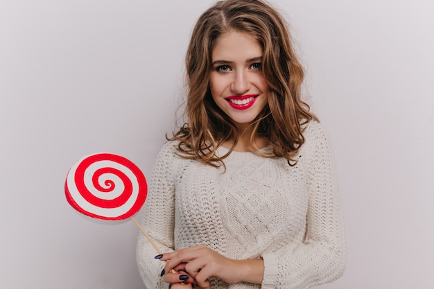 Nice girl with blue eyes and red lipstick is smiling and holding lollipop in her hands on white wall