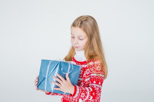 크리스마스 선물을 가진 좋은 여자. 귀여운 아이, 아이는 선물을 들고 빨간 니트 북유럽 스웨터를 입는다