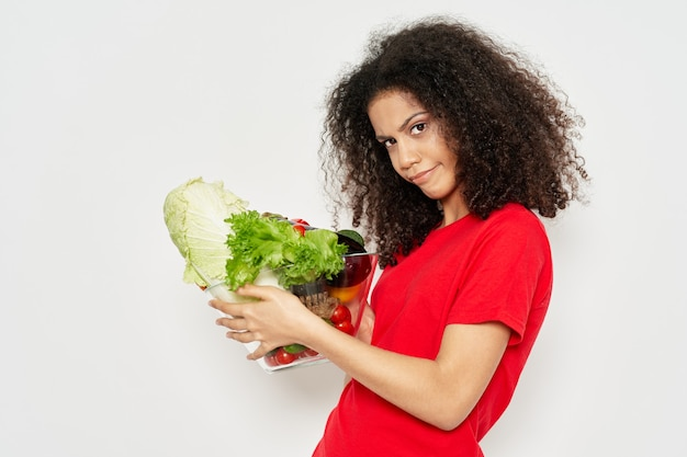 Nice girl with curly hair and a red tank top salad