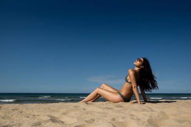 Nice girl with a green bikini getting tanned on the beach