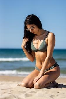 Nice girl with a green bikini touching her hair on the beach