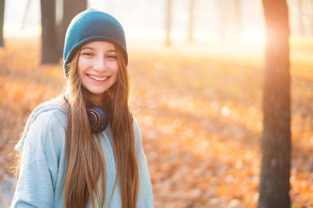 秋の自然の中でヘッドフォンを持つ素敵な女の子
