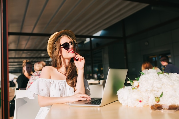 Nice girl with long hair in hat sits at  table on the terrace in cafe . she wears a white dress with bare shoulders, red lipstick, sunglasses . she looks happy at work with laptop.