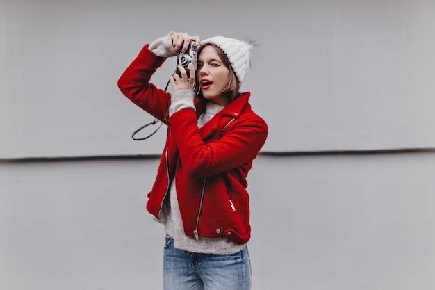 レトロなカメラで赤い口紅の写真を持つ素敵な女の子。暖かいショートコート、ジーンズ、灰色の背景にニット帽の女性の肖像画。