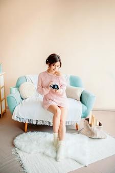 Симпатичная девушка со старинной камерой на светлом уютном фоне