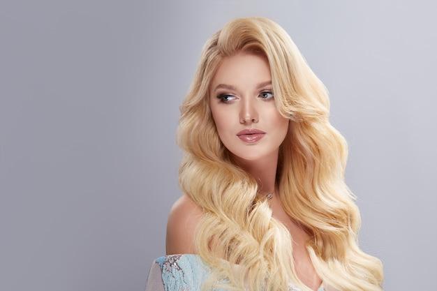 Симпатичная девушка с белыми вьющимися волосами смотрит в сторону