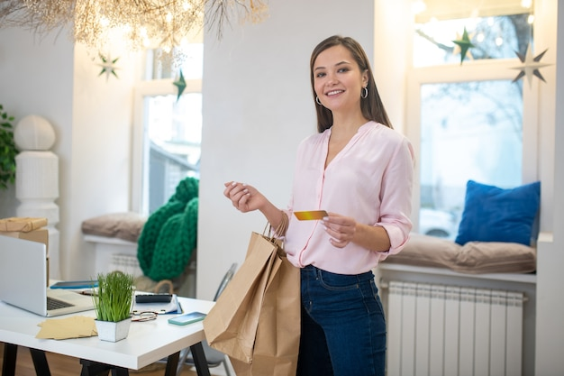 Nice good looking woman holding her bank card while spending money during shopping