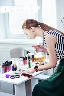 Nice good looking woman putting on her makeup while wanting to be beautiful