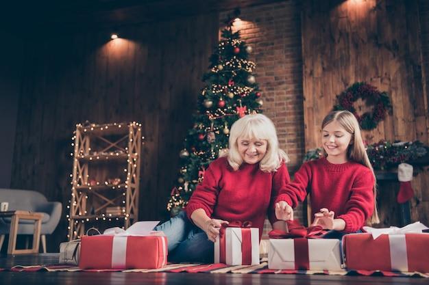 素敵なおばあちゃんの孫は、装飾されたレンガの木のインテリアハウスで床のオープンボックスに座っています