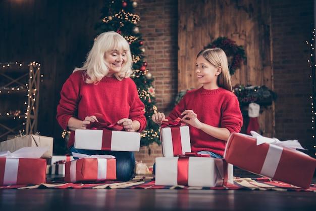 素敵なおばあちゃんの孫は、装飾されたレンガの木のインテリアハウスでフロアパックの贈り物を座っています