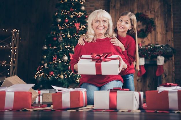 素敵なおばあちゃんプレティーンの孫が床に座って装飾されたロフトスタイルのインテリアハウスで贈り物を保持します
