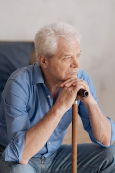 Nice grey haired pensive man sitting and leaning on the walking stick while being involved in his thoughts