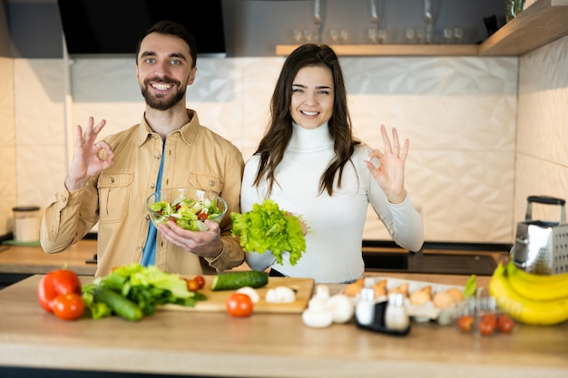 Симпатичный парень и милая девушка с красивой улыбкой показывают, что они предпочитают овощи мясу, чтобы спасти животных.