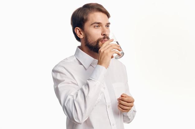 유리에서 물을 마시고 손으로 몸짓을하는 멋진 남자