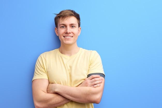 파란색 배경 위에 절연 카메라 웃는 캐주얼 티셔츠에 좋은 사람, 팔 접혀, 젊은 남성 서 넘어. 사람, 라이프 스타일 개념