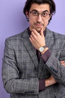 あごに手をつないでカメラのポーズを見てトレンディなスーツと眼鏡のナイスガイ。ビジネスマンの概念。