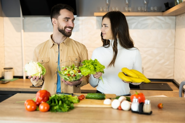 Nice guy and lovely girl with pretty smile are showing that they prefer vegetables to meat to save animals.
