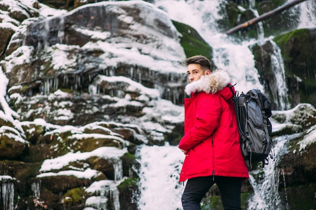 Nice guy model posing near the waterfall in winter mountains