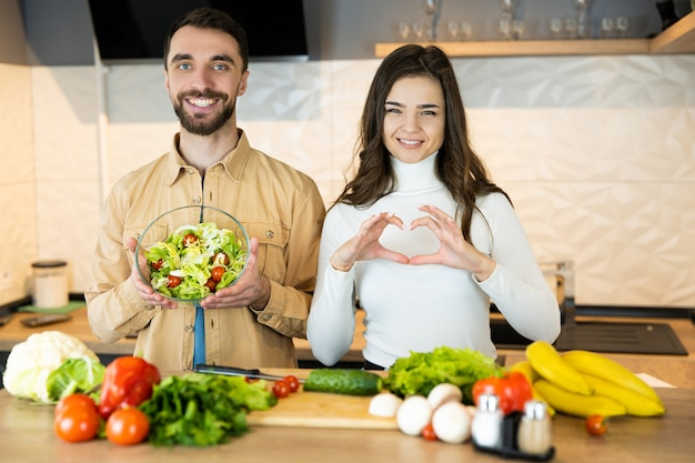 Nice guy and sweet girl with pretty smile are showing that they prefer vegetables to meat to save animals.