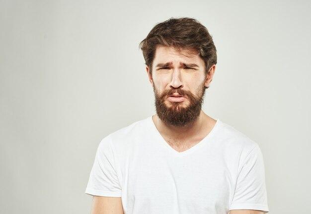悲しい顔の明るい背景のトリミングされたビューに白いtシャツのひげを持つナイスガイ