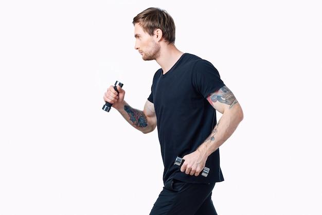 黒のtシャツとズボンのダンベルを持ったナイスガイがスポーツの側面図に入る