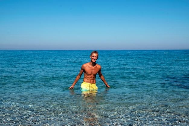 Симпатичный парень с сексуальной прессой улыбается в море. отдых в море. летнее время