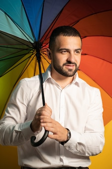 A nice guy with a stylish beard and white shirt stands with a rainbow umbrella behind his back. handsome guy in support of lgbt society.