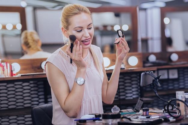 良い髪形。化粧品についての撮影ビデオを楽しんでいる素敵な髪型の若いファッショナブルな女性