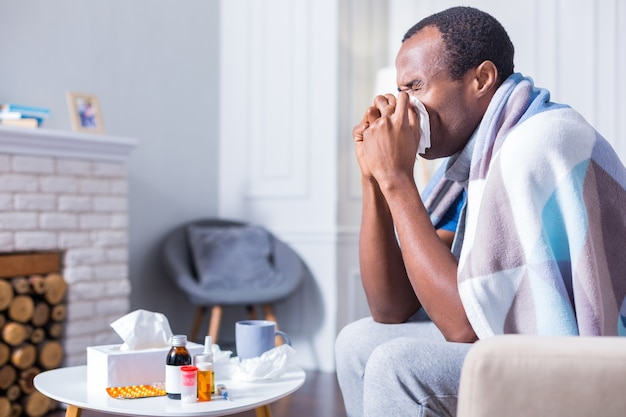 Nice handsome adult man sitting on the sofa and holding a paper tissue while sneezing